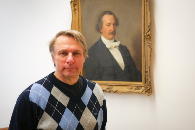Suomen Taiteilijaseuran puheenjohtaja Markus Renvall. Seinällä Suomen Taiteilijaseuran ensimmäinen puheenjohtaja Zachris Topelius.