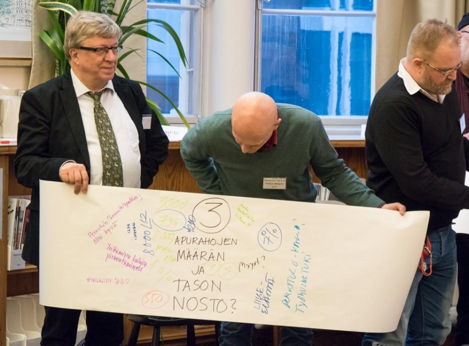SDP:n Thomas Wallgren tarkistaa, mitä tulikaan kirjoitettua. Kuvataiteilija nyt! -vaalipaneeliin Helsingin Rikhardinkadun kirjastossa osallistuivat myös keskustan Timo Laaninen ja SKP:n JP Väisänen.